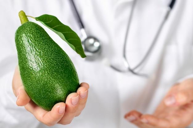 栄養士の医者は新鮮なアボカドを手に持っています。健康食品のコンセプト