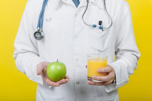 Диетолог доктор мужчина держит стакан сока и яблоко
