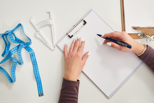 Nutritionist doctor writing diet plan on table with measuring tape, view from above