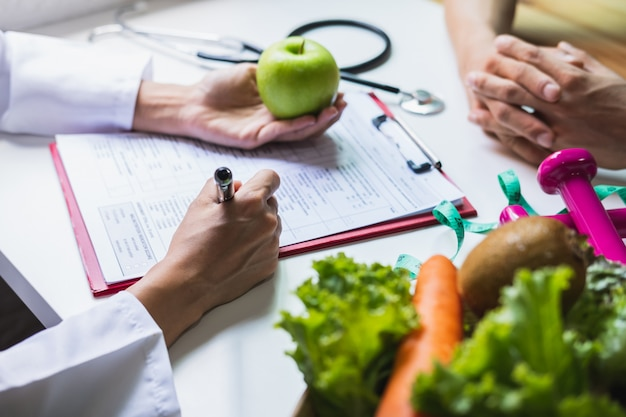 Nutritionist giving consultation to patient with healthy fruit and vegetable, right nutrition and diet