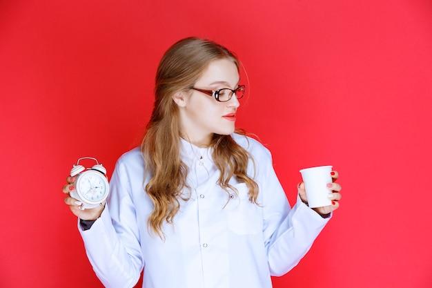 Диетолог держит чашку напитка и будильник, указывая время.