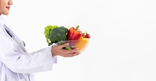 Диетолог держит миску со многими свежими овощами и фруктами с высоким содержанием витамина с