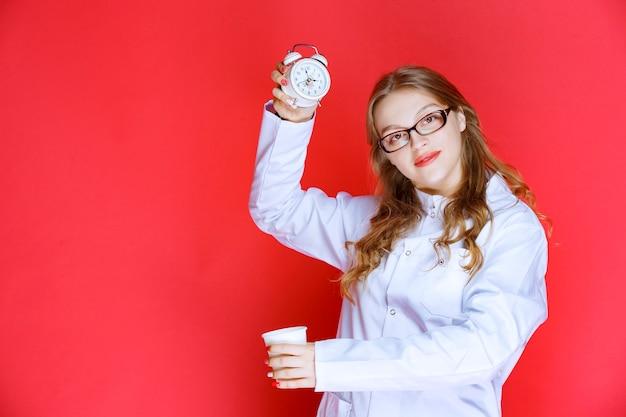 Nutrizionista che tiene una tazza di bevanda e una sveglia che indica l'ora.