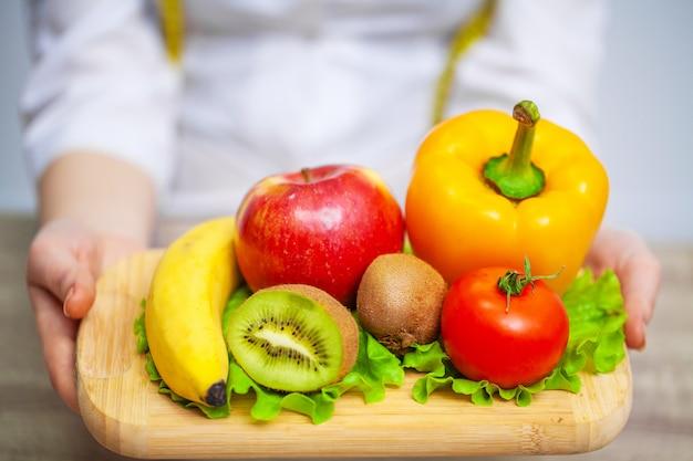 Диетолог держит свежие фрукты и овощи для здорового питания