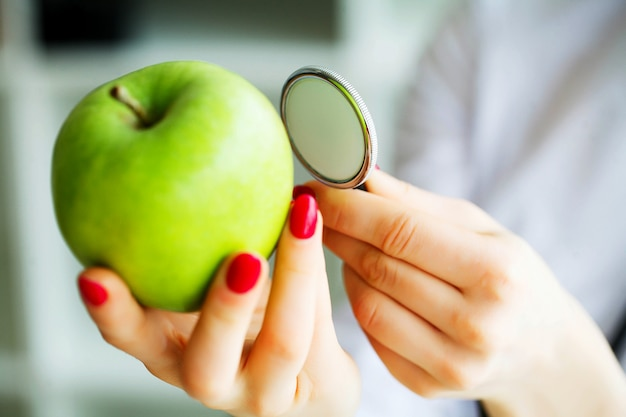 The nutritionist holds in the hands of fresh green apple.