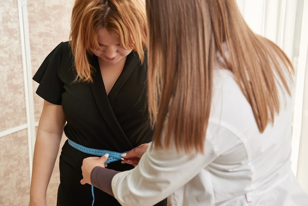 Nutritionist measuring teenager with tape in weight loss clinic
