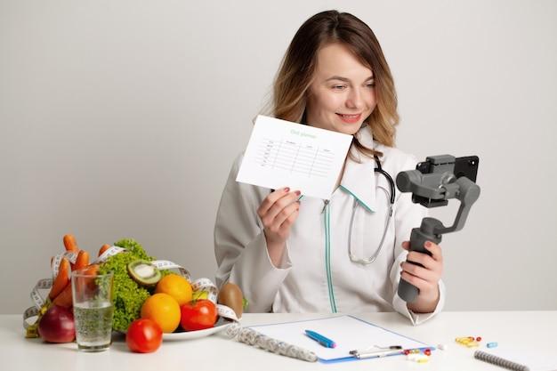 栄養士は、携帯電話での健康的な食事についてのビデオブログを記録しています。
