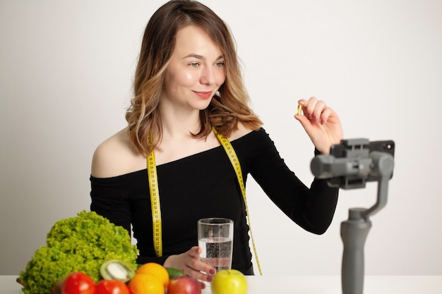 Nutritionist records a video blog about healthy eating on a mobile phone.