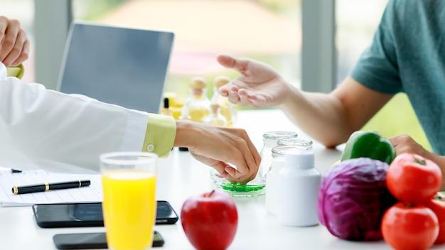 영양사의 손이 환자에게 보여주기 위해 탁자 위의 병에서 녹색 알약을 움켜쥐고 있습니다. 과일과 야채, 주스, 노트북, 영양사 사무실 테이블에 휴대 전화.