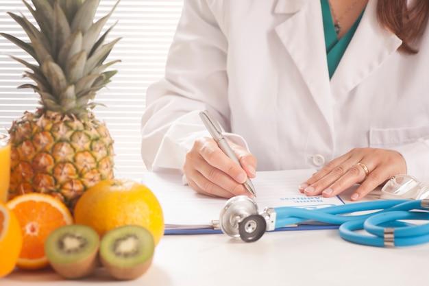新鮮な果物で医療記録と処方箋を書く栄養士 Premium写真