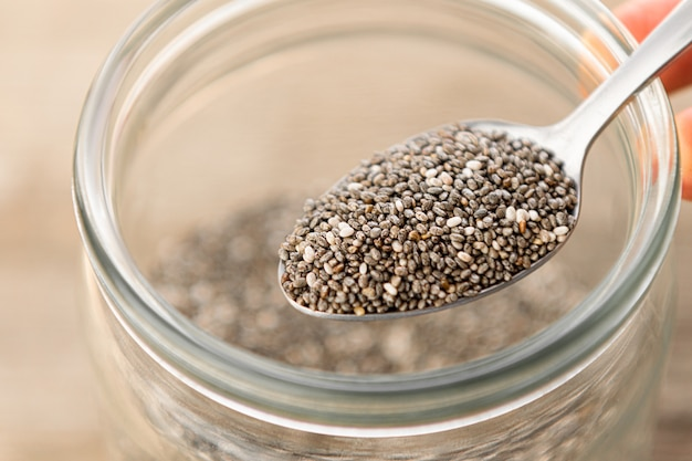 Nutritious chia seeds on a spoon, close up.
