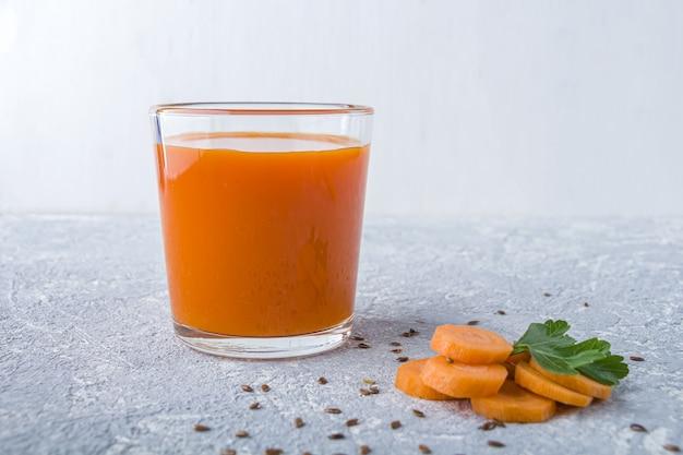 亜麻仁種子とパセリの葉とガラスの栄養価の高いデトックスキャロットジュース。アルカリダイエットのコンセプトです。オーガニックベジタリアンドリンク
