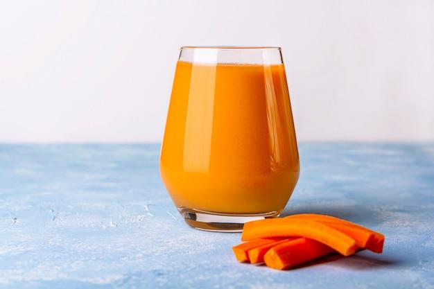 栄養価の高いデトックスニンジンスムージー。新鮮な有機菜食主義者の飲み物とニンジンのスライス。健康的な食事のコンセプトです。適切な栄養、フィットネスダイエットの概念。グラスにオレンジジュース。