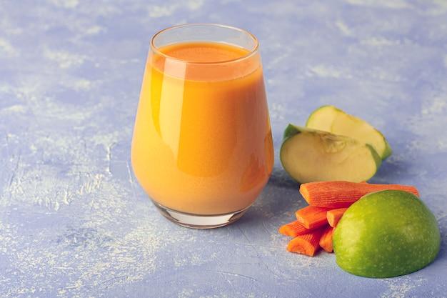 栄養価の高いデトックスニンジンスムージー。有機ベジタリアンドリンクとにんじんと青リンゴのスライス。健康的な食事のコンセプトです。適切な栄養、フィットネスダイエットの概念。