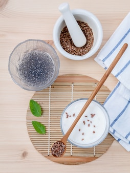 Nutritious flax seeds with yogurt  setup on wooden background .