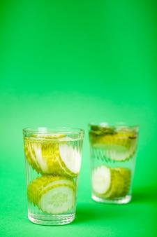 녹색 배경에 유리잔에 담긴 유기농 오이로 만든 영양가 있는 신선한 홈메이드 디톡스 물