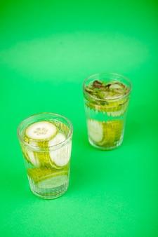 녹색 배경에 두 잔에 담긴 유기농 오이로 만든 영양가 있는 신선한 홈메이드 디톡스 물