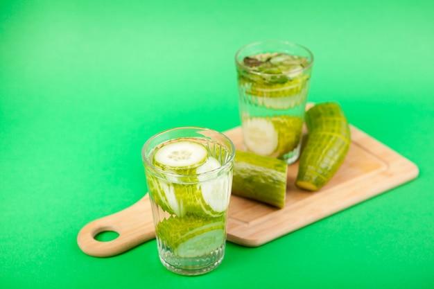 Nutriente acqua disintossicante fatta in casa dai cetrioli organici in due bicchieri su uno sfondo verde