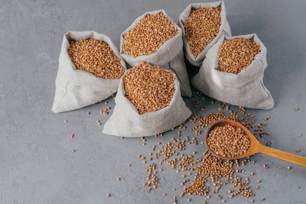 Nutritious ingredient containing vitamins. shot of linen sacks with buckwheat against grey background. organic food. healthy nutrition