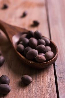 영양가 있는 로터스 씨앗은 나무 숟가락에 있는 카말 카타와 원시 형태의 황마 가방, 선택적 초점