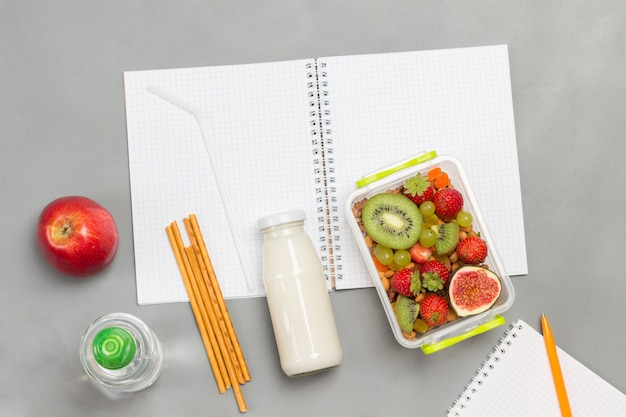 Nutritious lunch box of fruits, berries and nuts, bottle of yogurt and edible straws