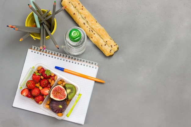 Nutritious lunch box of fruits, berries and nuts on open notebook with bottle of water and bowl of pencils