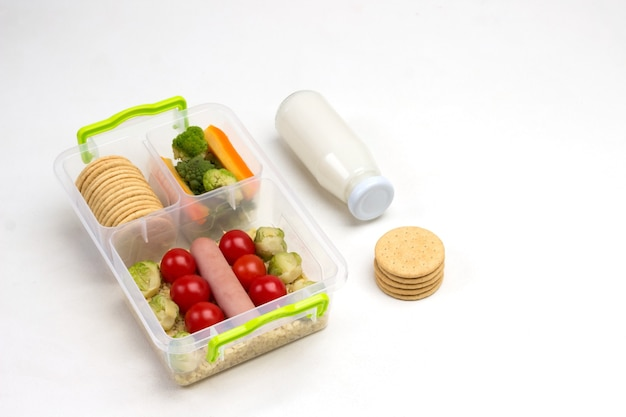 Nutritious lunch box with vegetables and sausage and bottle of yogurt and cookies on white.