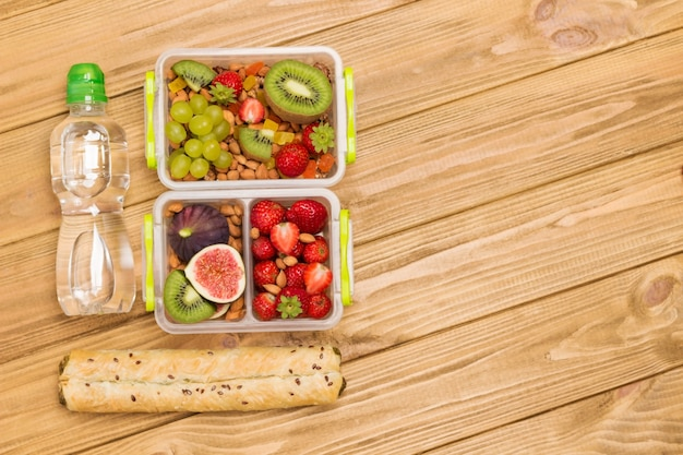Nutritious lunch boxes with fruits, berries and nuts and bottle of water