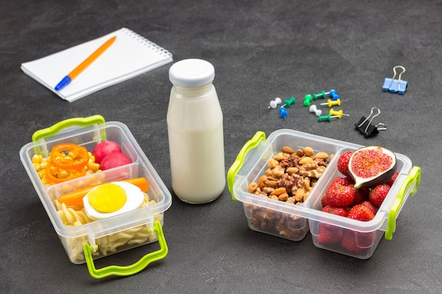 Nutritious lunch boxes with of fruits, and nuts and colorful stationery.