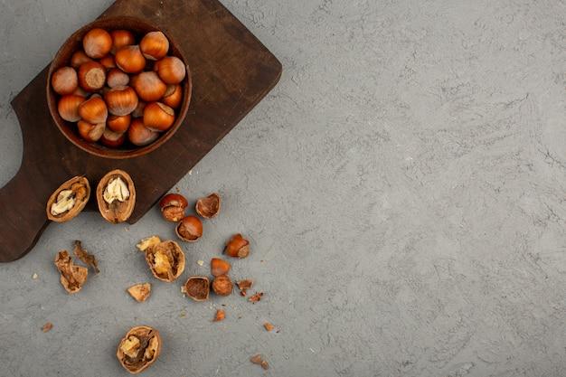 ナッツ、ヘーゼルナッツ、クルミの全体と木製の机と灰色の床に皮をむいた