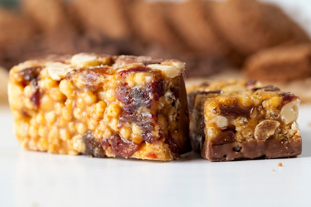 チョコレートバーのナッツ、エアライス、チョコレート、その他の材料、さまざまな材料の食品のクローズアップ、高カロリーのエネルギーバー