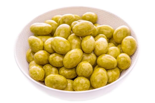 Орехи миндаль в глазури из зеленого чая матча в белой тарелке на белом фоне, изолированные предметы и продукты