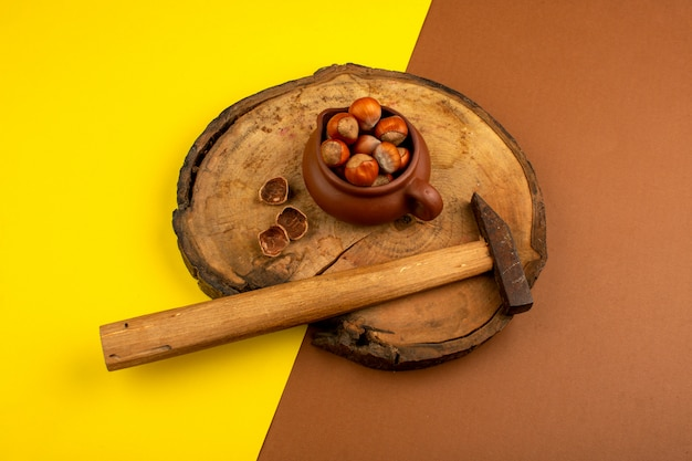 Nuts along with hammer on a wooden desk and yellow-brown