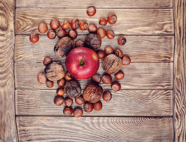 ナッツと木製のテーブルの上のリンゴ、中央のリンゴに焦点を当てる