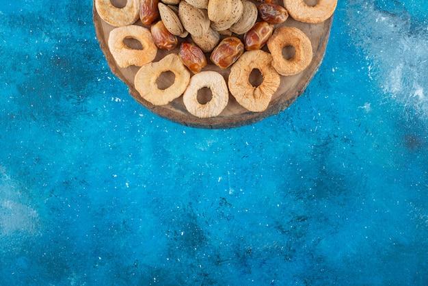 Орехи и сухофрукты на доске, на синем столе.