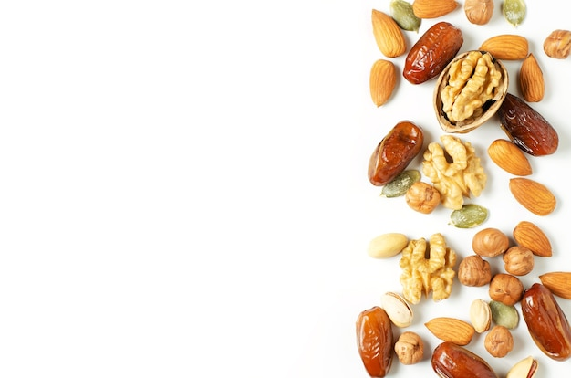 白い背景の上のナッツとドライフルーツ。抗酸化物質とビタミンの供給源。健康的な食事。フラットトップビュー。スペースをコピーします。