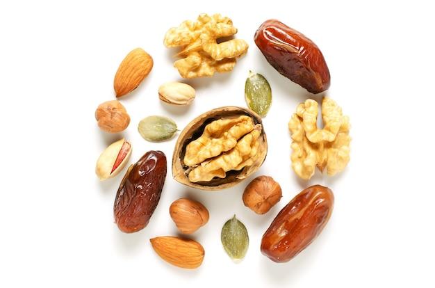 白い背景の上のナッツとドライフルーツ。抗酸化物質とビタミンの供給源。健康的な食事。フラットトップビュー。