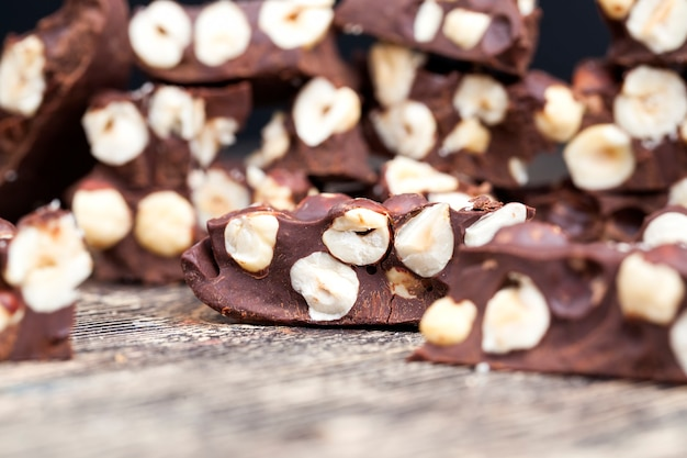 ヘーゼルナッツ入りチョコレート、ヘーゼルナッツ入りのおいしいミルク自家製チョコレートの製造におけるナッツと天然カカオ製品