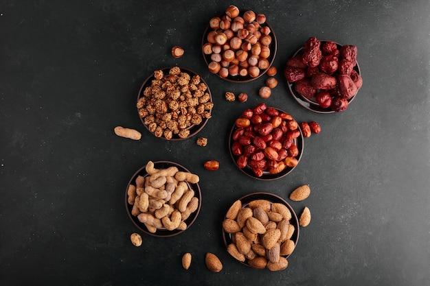 黒受け皿のナッツとスナック、上面図。