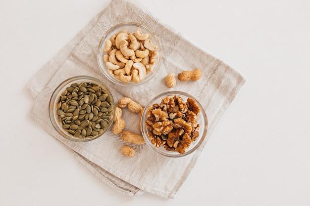 白いテーブルの上のリネンティータオルにナッツと酢。適切な栄養のためのクルミ、カシューナッツ、カボチャの種。脳と体のための健康食品と栄養素