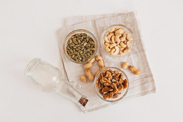 흰색 테이블에 린넨 차 수건에 견과류와 식초. 적절한 영양을 위한 호두, 캐슈 및 호박씨. 두뇌와 몸에 좋은 음식과 영양소
