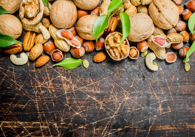 ナッツの背景。緑の葉を持つさまざまな種類のナッツ。木製の背景に。