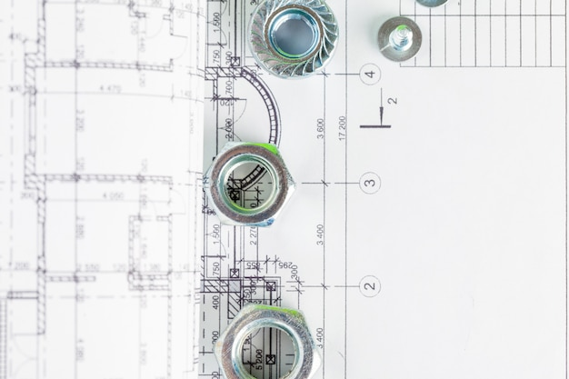 Nuts and bolts close-up over house plan