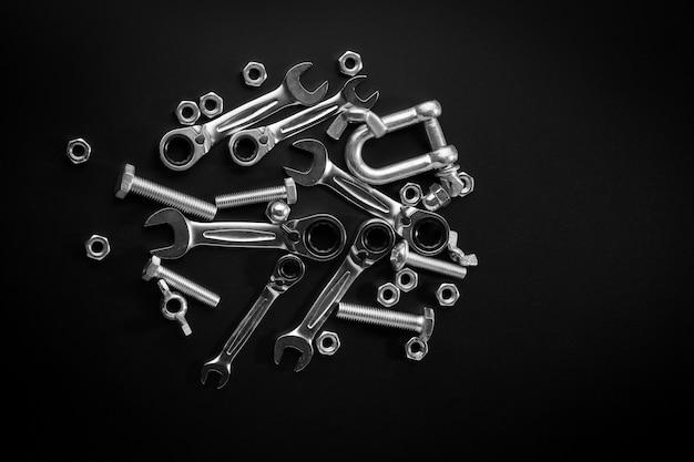 暗い背景にナット、ボルト、レンチ、ラチェット。ボルト接続を固定するためのツール。