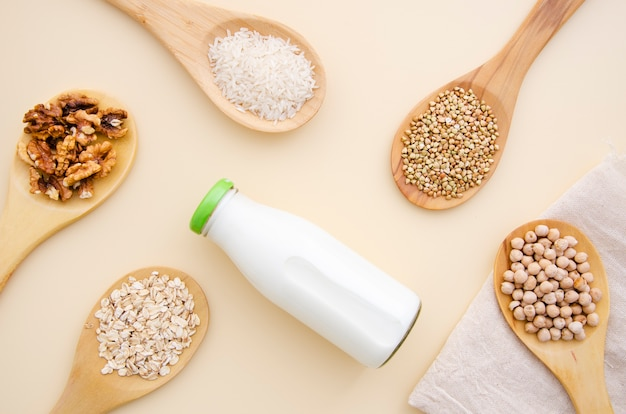 Nuts and cereals arranged in wooden spoons around a bottle of milk
