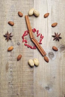 Орехи, палочки корицы и звездчатый анис в виде часов на деревянном столе