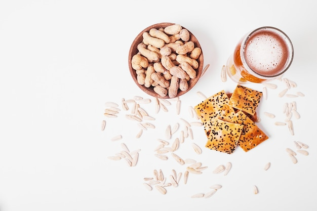 Nuts and crackers with beer on white.