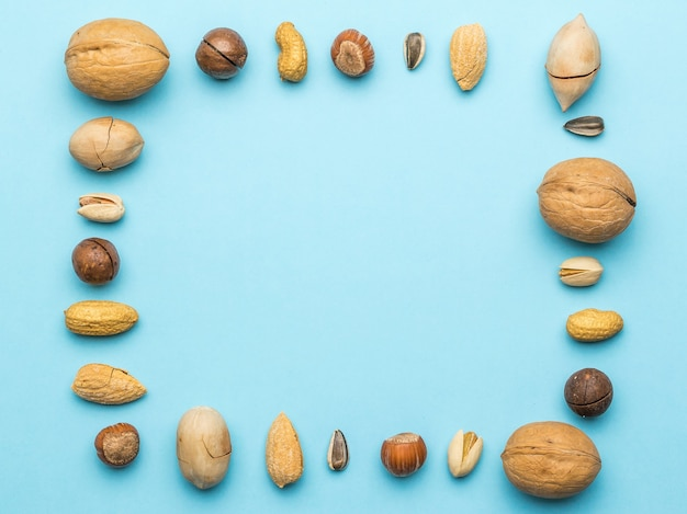 Nuts of different varieties in the form of a frame on a blue . vegetarian food.