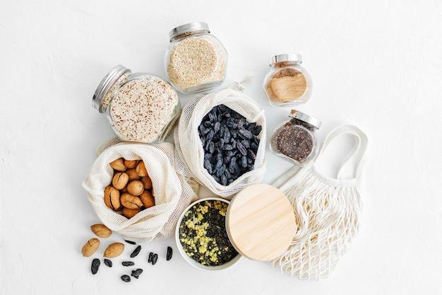 Орехи, сухофрукты и крупы в мешках из эко-хлопка и стеклянных банках на белом столе на кухне. покупки продуктов с нулевыми отходами. безотходная жизнь