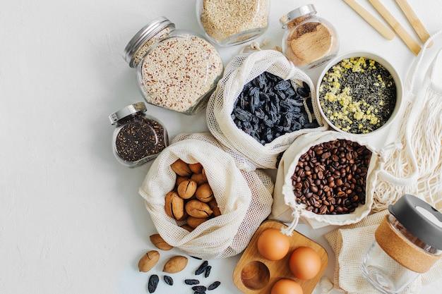 キッチンの白いテーブルにエココットンバッグとガラスの瓶に入ったナッツ、ドライフルーツ、ひき割り穀物。ゼロウェイストフードショッピング。無駄のない生活